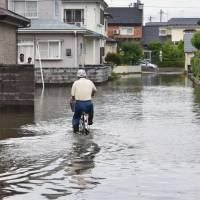 A man rides his bicycle through floodwaters in the city of Akita on Sunday. | KYODO