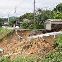A road in the city of Masuda, Shimane Prefecture, collapsed due to heavy rain that fell across the region Wednesday morning. | KYODO