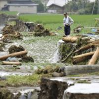 A man looks at a rice field flooded by heavy rain on Saturday in the village of Toho, Fukuoka Prefecture. | KYODO