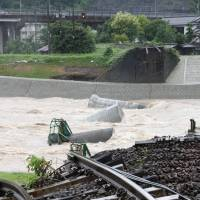 A railway bridge over a river in the city of Hita, Oita Prefecture, was washed away by torrential rain which hit the area on Wednesday and Thursday. | KYODO