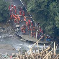 Rescuers face a pile of timber and other debris near the village of Toho in Fukuoka Prefecture as they try to find those still unaccounted for on Saturday. | KYODO