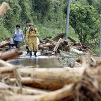 Residents of the city of Fukuoka walk through water and debris as they carry items to relatives in an isolated area of the village of Toho on Saturday. | KYODO