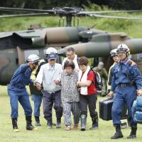 A woman is helped to safety after being airlifted from her home in Asakura, Fukuoka Prefecture, on Friday morning, amid flooding caused by torrential rain that began Wednesday. | KYODO