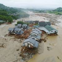 Houses are flanked by rivers of water, mud and debris in Asakura, Fukuoka Prefecture, on Friday after days of heavy rain. | KYODO