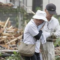 A woman cries Thursday after the body of a relative is found under mud and debris that damaged houses in Asakura, Fukuoka Prefecture, following days of record rainfall in Kyushu. | KYODO