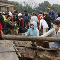 Residents remove timber and other debris in Asakura, Fukuoka Prefecture, as they search for missing people following heavy flooding Thursday. | KYODO