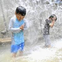 Children play under jets of water at a Tokyo park on Wednesday. The Meteorological Agency said the rainy season appears to have ended across much of Japan, including in Tokyo.   KYODO