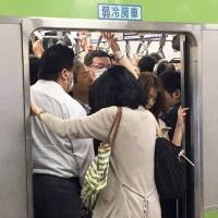 Passengers squeeze into a morning rush-hour train on the Yamanote Line, one of the busiest lines in the heart of the capital, at JR Tokyo Station on June 28.   YOSHIAKI MIURA