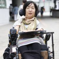 Kaoru Ishiji uses a wheelchair in Kobe in June. She calls for an inclusive society without discrimination. | KYODO