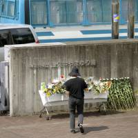 A visitor offers flowers at the gate of the Tsukui Yamayuri En care home in Sagamihara, Kanagawa Prefecture, in July 2016 in the wake of the mass murder of residents with intellectual disabilities at the facility. | KYODO