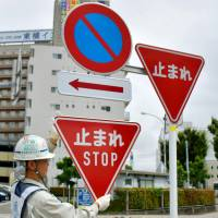 A traffic sign is replaced with a bilingual one in Osaka on Saturday.   KYODO