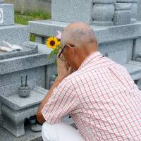 A man visits the grave of his son, who committed suicide due to overwork seven years ago, in Kochi on Saturday. | KYODO