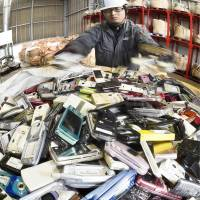 Tokyo Olympics organizers are collecting used mobile phones like these piled up at a recycling factory in Kitakyushu to turn the precious metals they contain into Olympic medals. | KYODO