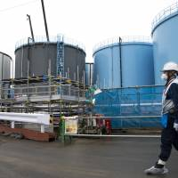 An employee walks past storage tanks for contaminated water at the tsunami-crippled Fukushima No. 1 nuclear power plant of the Tokyo Electric Power Co. in Okuma, Fukushima Prefecture, in February. Tepco needs to release the water — which contains radioactive tritium that is not removable but considered not harmful in small amounts — into the Pacific Ocean, Chairman Takashi Kawamura said. | TOMOHIRO OHSUMI / POOL PHOTO / VIA AP, FILE