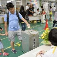A voter casts his ballot at a polling station for the Tokyo Metropolitan Assembly election in Minato Ward on Sunday. | KYODO