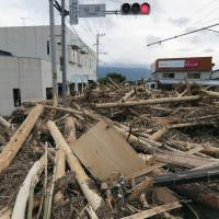 A road is blocked with driftwood and other debris in the city of Asakura, Fukuoka Prefecture, on Tuesday following torrential rain in the Kyushu region, hampering efforts to rescue people and restore services. | KYODO
