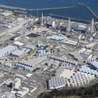 The Fukushima No. 1 plant and hundreds of tanks containing tritiated water are viewed from the air in February. | KYODO