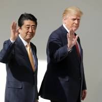U.S. President Donald Trump and Prime Minister Shinzo Abe wave while walking to a joint news conference in the East Room of the White House in Washington in February. | BLOOMBERG