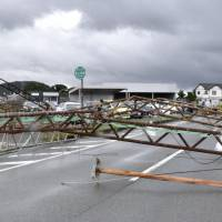 A metal structure blocks a road in Kumamoto Prefecture after being knocked down by strong winds associated with Typhoon Nanmadol on Tuesday morning. The typhoon, the third of the season, made landfall in Nagasaki Prefecture. | KYODO