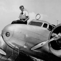 Amelia Earhart sits on the nose of her aircraft before takeoff in Miami in 1937. | AP