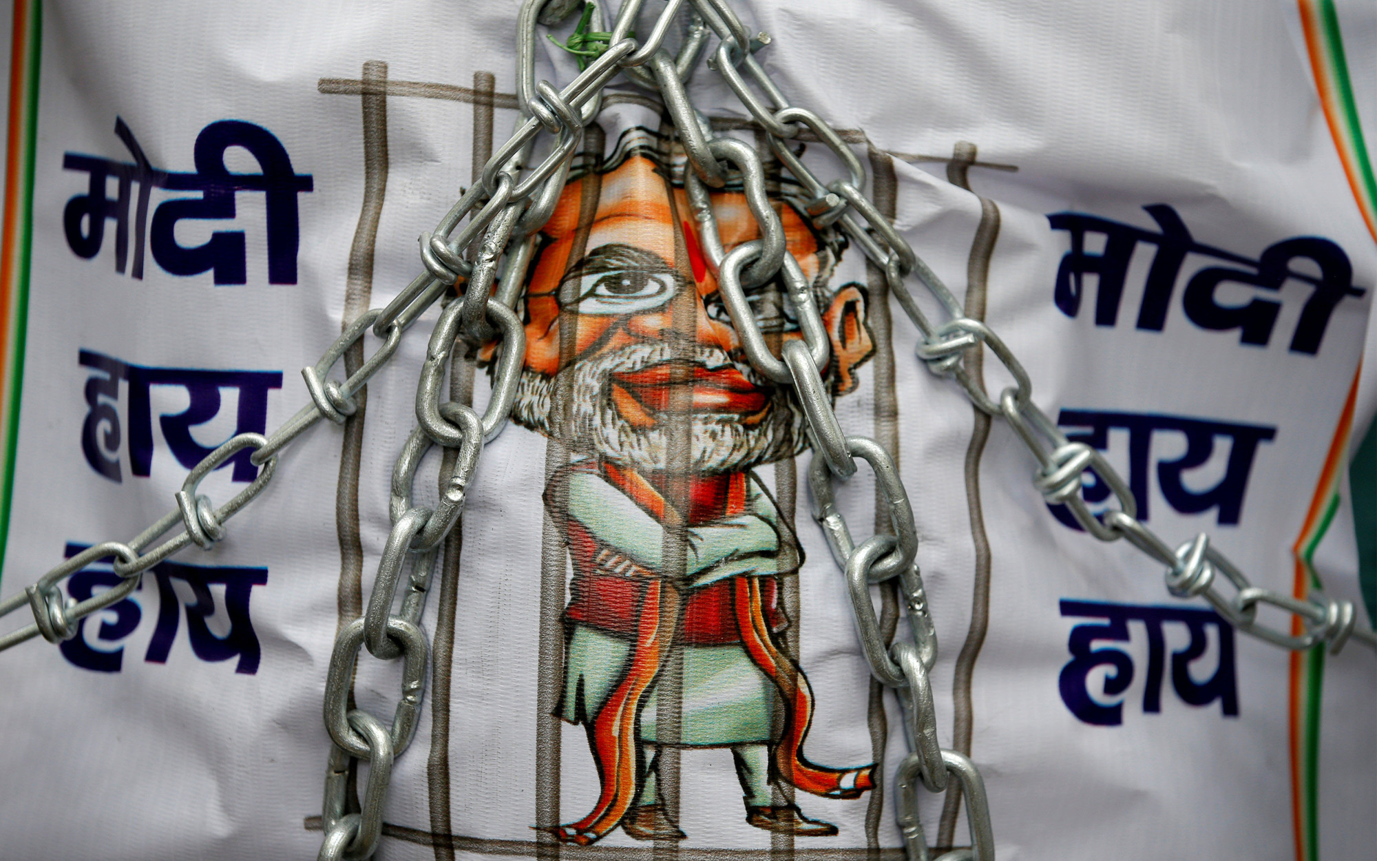 A banner depicting Indian Prime Minister Narendra Modi in prison is displayed during a protest against the introduction of the goods and services tax (GST) in New Delhi  on July 18. | REUTERS