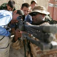 A British soldier lets Afghan children look through the sights on his rifle during a patrol through a neighborhood in central Kabul in July 2006. | BLOOMBERG