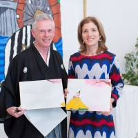 Well played: Peter MacMillan presents a specially made image of poem cards, featuring the Kennedy family tartan check in the costume of the poet, to Ambassador Caroline Kennedy at the U.S. Embassy in Tokyo in January.