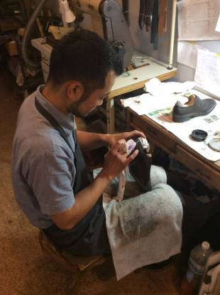 Apprentice Amane Yamaguchi polishes a pair of hand-crafted shoes.
