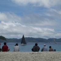 Under sail: People watch from Furuzamami Beach as the yachts tack round the Furuzamami buoy, located just 40 meters off shore. | OSCAR BOYD