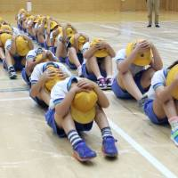 Preparing for the worst: Children at an elementary school in Takaoka, Toyama  Prefecture, take part in an incoming ballistic missile evacuation drill on July 14. | KYODO