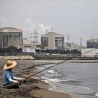 A man fishes in front of the Wolsong Nuclear Power Plant in Gyeongju, South Korea. Last month, President Moon Jae-in promised to scrap plans for new nuclear plants, not extend the life of existing ones, shut down 10 old coal power plants and cancel new coal projects. | BLOOMBERG