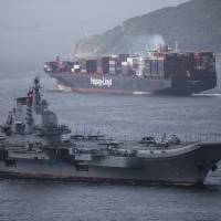 The Chinese aircraft carrier Liaoning sails past a container ship near Hong Kong on July 7. China is utilizing its considerable economic clout and growing military might to advance its foreign policy objectives. | BLOOMBERG