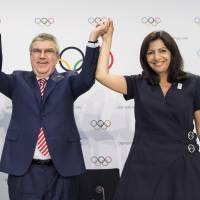Mayor of Los Angeles Eric Garcetti (left), International Olympic Committee President Thomas Bach, and Mayor of Paris Anne Hidalgo during a press conference after the IOC Extraordinary Session, at the SwissTech Convention Centre, in Lausanne, Switzerland on July 11. | AP