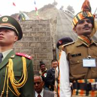 A Chinese soldier and an Indian soldier maintain ceremonial positions marking the borders of their respective countries at the 2006 opening of the Nathu La pass in the northeastern Indian state of Sikkim, which had been closed following military clashes between China and India in 1967. Border tensions are rising  once again between the two Asian giants. | AP