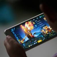 A child plays 'Honour of Kings' by Tencent at home in Dezhou, Shandong province, on July 2. Last week the video game, which is played by roughly one in seven Chinese, was singled out by the People's Daily for an unusually high-profile criticism. | REUTERS