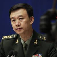 Chinese defense ministry spokesman Wu Qian speaks at a news conference in Beijing on Monday. China is warning India not to underestimate its determination to safeguard what it considers sovereign territory amid a standoff over a contested region in the Himalayas. | AP