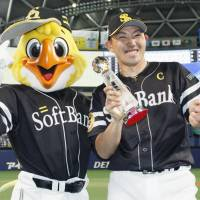Game 1 MVP Seiichi Uchikawa and the Hawks mascot share a smile on Friday night. | KYODO