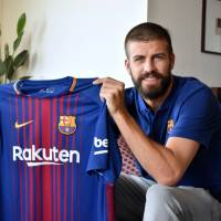 FC Barcelona defender Gerard Pique displays the team's new shirt with the Rakuten logo during an exclusive interview with The Japan Times on Thursday. | SATOKO KAWASAKI