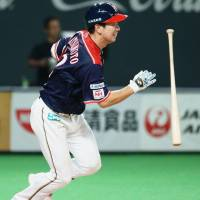 The Fighters' Go Matsumoto tosses his bat after connecting on a game-ending hit in the 11th inning against the Eagles on Thursday at Sapporo Dome. Hokkaido Nippon Ham defeated Tohoku Rakuten 4-3. | KYODO