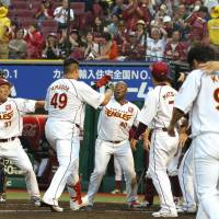 The Eagles begin to celebrate as Japhet Amador (49) crosses home plate after hitting a sayonara home run against the Buffaloes on Sunday in Sendai. | KYODO