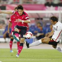 Cerezo Osaka's Kenyu Sugimoto shoots the ball against the Urawa Reds on Saturday night at Yanmar Stadium. Sugimoto finished with two goals in Cerezo's 4-2 victory. | KYODO