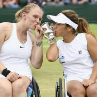 Yui Kamiji (right) and Jordanne Whiley kiss the trophy after winning their fourth consecutive women's wheelchair title at Wimbledon on Sunday. | KYODO