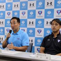 Dome Corporation CEO Shuichi Yasuda, who will be the leader of the University of Tsukuba's athletic department formation task force, speaks to the media while university officials Yukio Yamada (left) and Tsuyoshi Matsumoto look on Thursday at the school's Tokyo campus. | KAZ NAGATSUKA