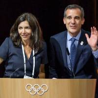 Paris Mayor Anne Hidalgo (left) and Los Angeles Mayor Eric Garcetti wave from the podium during an IOC extraordinary session on Tuesday in Lausanne, Switzerland. | AFP-JIJI