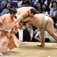 Takayasu (right) shoves Ikioi out of the ring at the Nagoya Grand Sumo Tournament on Monday. | KYODO