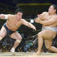 Harumafuji (left) has inflammation in his left elbow that may require surgery. | KYODO