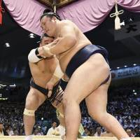 Yokozuna Harumafuji (left) grapples with Ikioi on Friday at the Nagoya Grand Sumo Tournament. Harumafuji improved to 4-2 with the victory. | KYODO