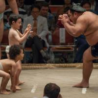 Shohozan faces off against two children during the Ozumo Beyond 2020 event on Oct. 4, 2016 at Ryogoku Kokugikan. | JOHN GUNNING