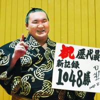 Yokozuna Hakuho celebrates his historic 1,048th career victory on Friday at the Nagoya Grand Sumo Tournament, moving past retired ozeki Kaio for first place on the all-time wins list. | KYODO