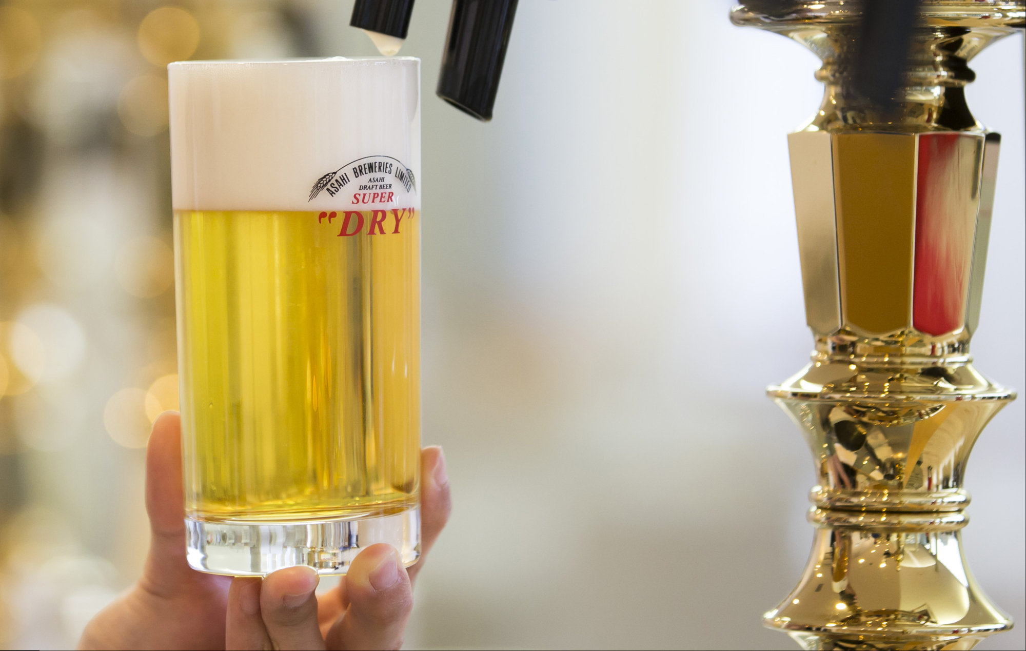 A bartender pours a glass of Asahi Super Dry beer. Asahi Group Holdings plans to sell its first bond in euros, following a $10 billion buying binge in Europe during the past year. | BLOOMBERG